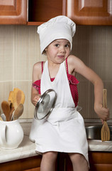 girl in a cap and an apron in kitchen
