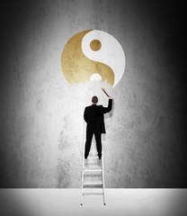 Work-life balance concept - man painting golden yin-yang symbol