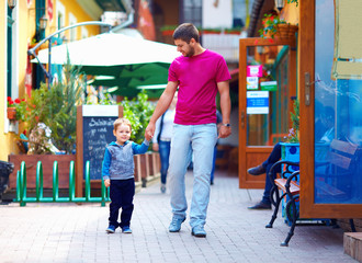 father and baby boy walking the city street