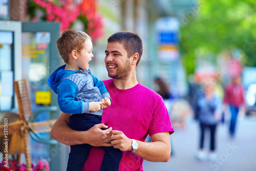 candid image of father and son walking crowded street