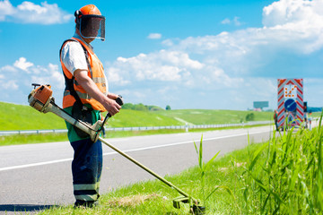 Road landscaper cutting grass along the road