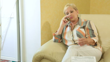 Mature woman doing paperwork on the phone at home