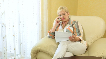 Mature woman talking on phone about finances