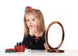 little girl rubs a cream face in the mirror
