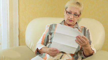 Senior woman reading some financial papers at home