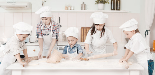 happy little chefs preparing dough in the kitchen with their