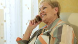 Mature woman chatting on the phone at home