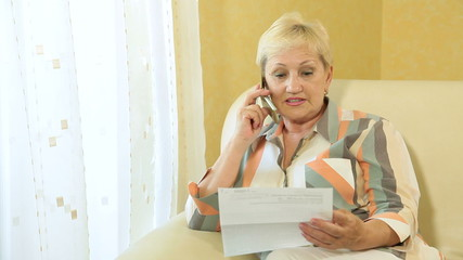Mature woman calling by the phone at home