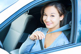 Smiling young woman in car fastens seat belt