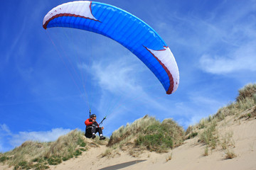 paraglider over sand dunes
