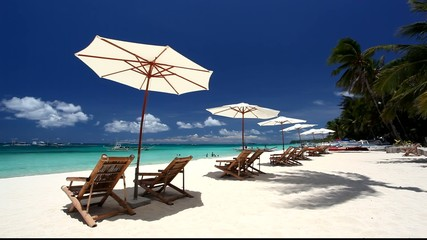 Sun umbrellas and beach chairs on coasline