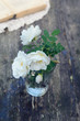 Dog rose flowers in a glass on rusted wooden table