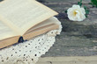 Open book on lace doily on rusted garden table