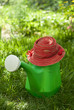 garden watering can and a hat