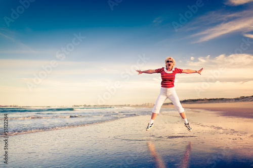 Senior woman enjoying beach holiday jumping in air
