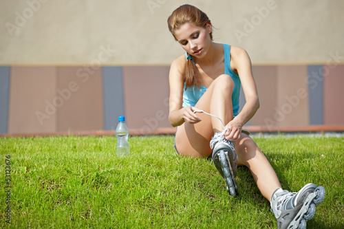 Woman skating in city. Girl going rollerblading sitting in grass