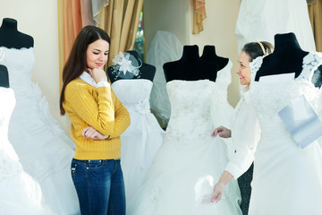 saleswoman helps girl chooses white bridal outfit