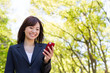 asian businesswoman using smart phone in the park