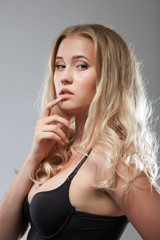 Charming curly blonde posing in studio, close-up