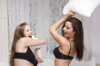 Two sexy girls having pillow fight on the bed