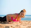 Frau macht Liegestütze am Strand