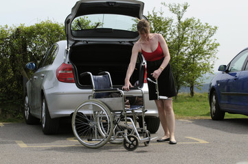 Woman erecting and putting together a wheelchair