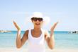 Ragazza sorridente con cappello bianco al mare