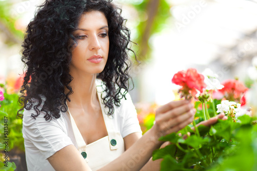 Female gardener in a greenhouse analyzing some flowers