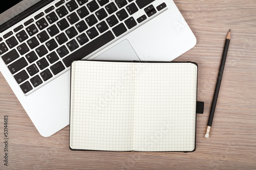 Notepad and laptop on wood table