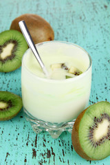 Delicious yogurt in glass with kiwi on wooden table close-up