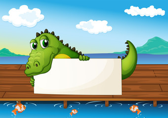 An alligator holding an empty signboard at the lake with fish