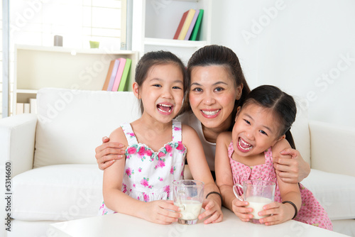 Mother and daughters drinking milk
