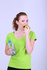 Beautiful young woman with bottle of water and apple