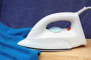 Electric iron and shirt, on white and blue background