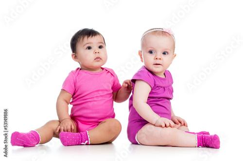 Funny babies girls sitting beside on floor
