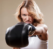 Portrait of sexy blonde sportish woman in boxing gloves