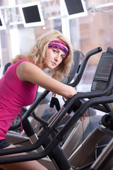 Beautiful blonde woman in pink sportswear on bike in gym