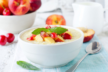 .Milk porridge with peaches and cherries