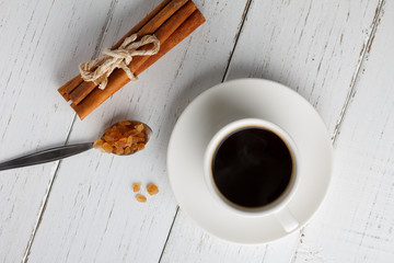 Coffee with caramel sugar and cinnamon on wooden table
