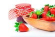 Strawberry berries in a wooden bowl with a jar of jam isolated o