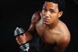 black athlete lifting weight. Male athlete performing biceps