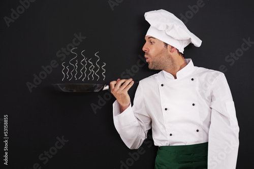 Chef blowing smoke from pan