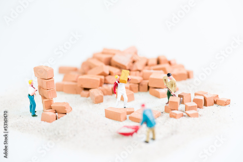 Miniature workmen working together in laying bricks