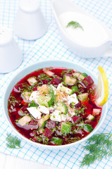 cold beetroot soup with cucumbers, eggs and herbs in a blue bowl