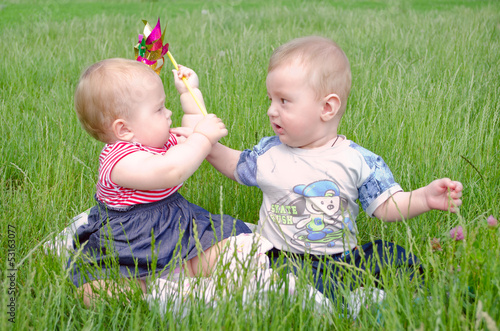 Little boy and girl playing on green grass