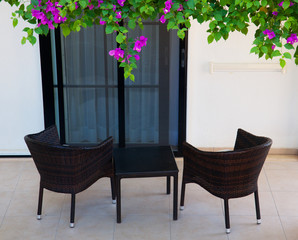 Wicker chairs on the terrace with flowers