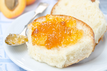 Sweet bun with apricot jam close-up