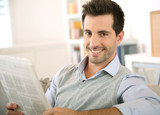 Man at home reading newspaper