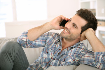 Young man at home talking on mobile phone
