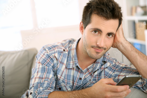 Handsome man using smartphone at home